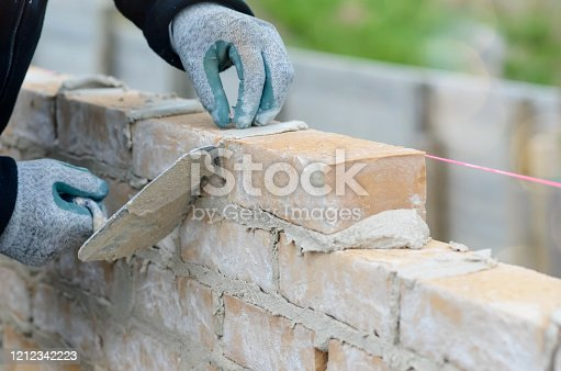 masons building a house in close up