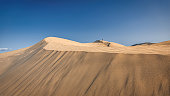 Panorama of the Sand Dunes of Maspalomas at Playa de Ingles Beach under blue cloudless summer sky. Young boy running up the sand dunes on the horizon. Maspalomas Dunes, Grand Canary, Canary Islands, Spain