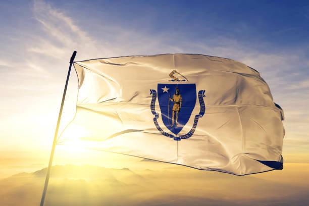 massachusetts staat van de verenigde staten vlag doek textielweefsel zwaaien op de bovenste zonsopgang mist mist - massachusetts stockfoto's en -beelden
