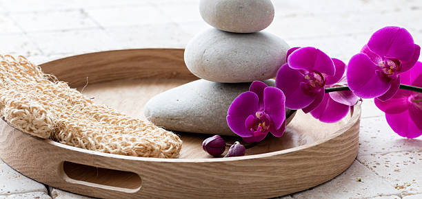 massage and exfoliation with loofah mitt, relaxing stack of stones - peeling bürste stock-fotos und bilder