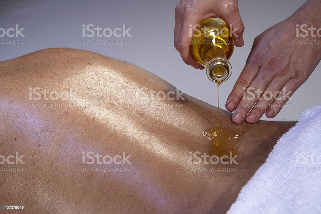 Massage for man: masseuse pouring oil on the back stock photo