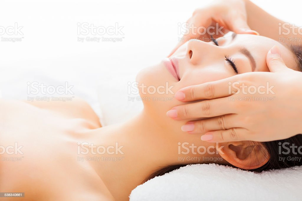 massage of face for woman in spa salon stock photo