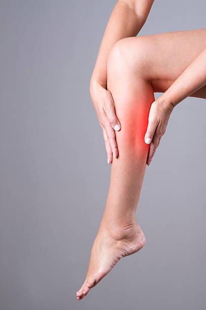 massage der weibliche bein auf einem grauen hintergrund - wadenkrämpfe was tun stock-fotos und bilder