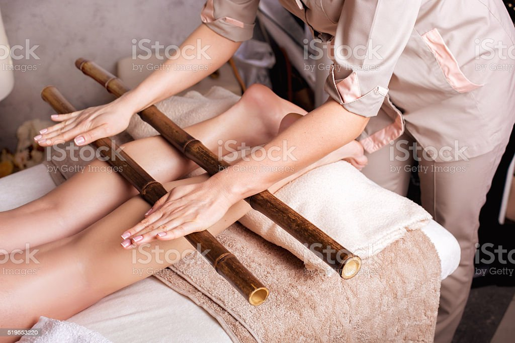 Massage of human foot in spa salon  with bamboo sticks stock photo