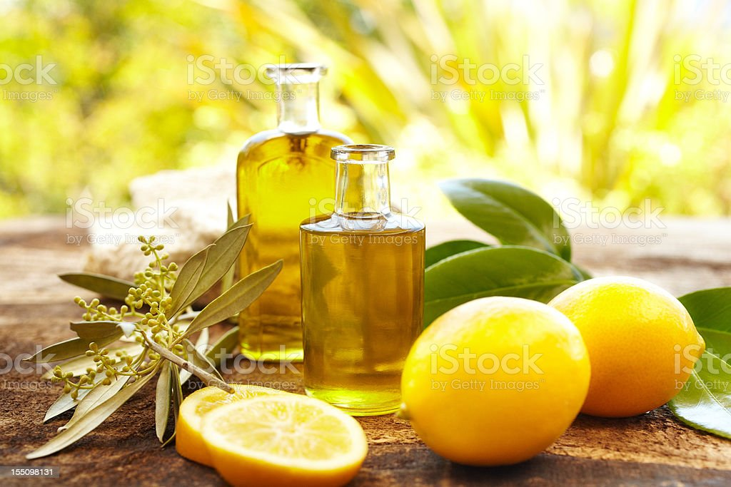 Massage oil bottles at spa outdoors with lemons stock photo