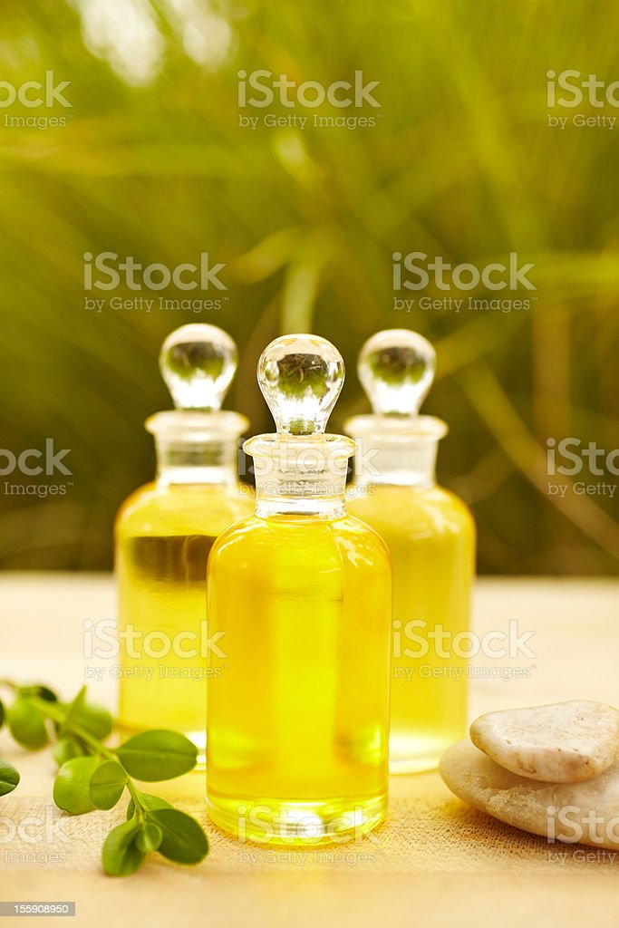 Massage oil bottles at spa with pebbles royalty-free stock photo