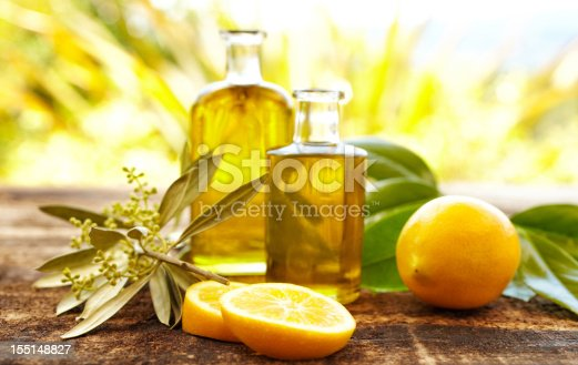 istock Massage oil bottles with lemons and olive branch 155148827