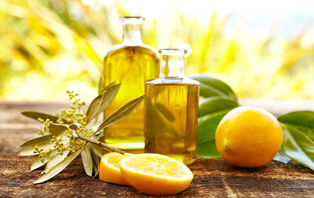 massage oil bottles with lemons and olive branch - aromatherapy stock photos and pictures