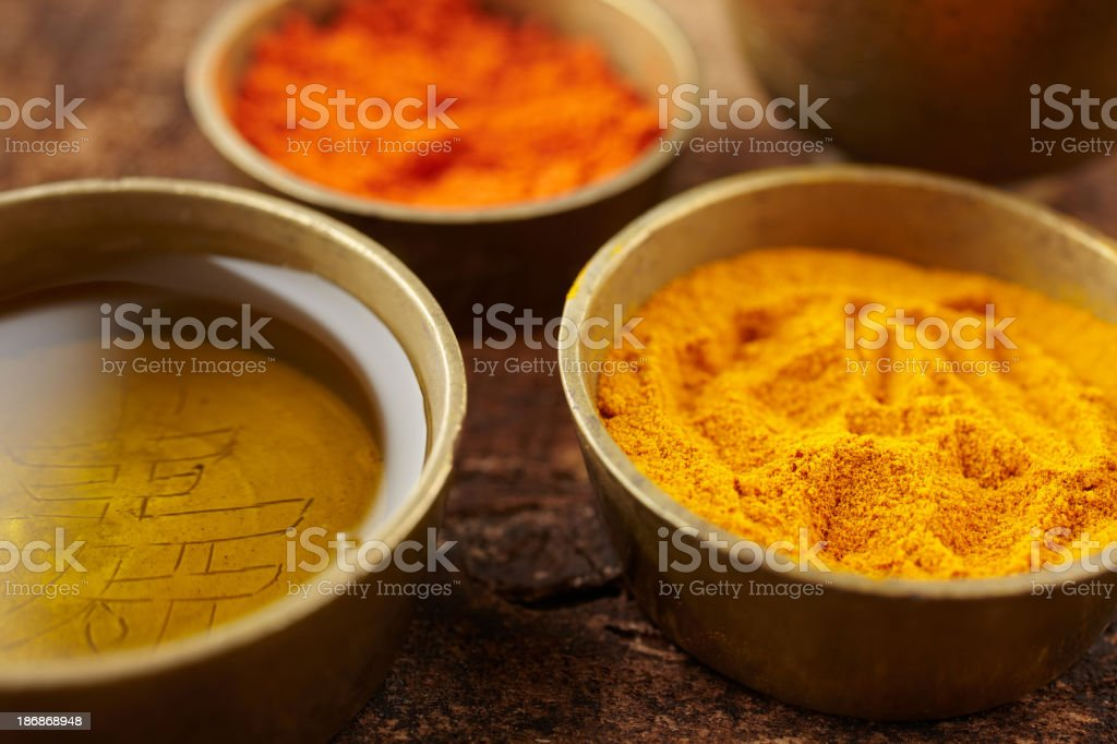 Massage oil turmeric and sandalwood powder in small copper bowls royalty-free stock photo