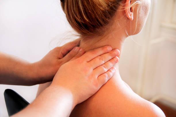 Massagem relax studio. Mulher tendo seu pescoço massageado por uma fisioterapeuta. Massagem terapeuta massageia os músculos do pescoço. Cuidados com o corpo. Linda garota relaxante com massagem no spa de beleza corpo. - foto de acervo