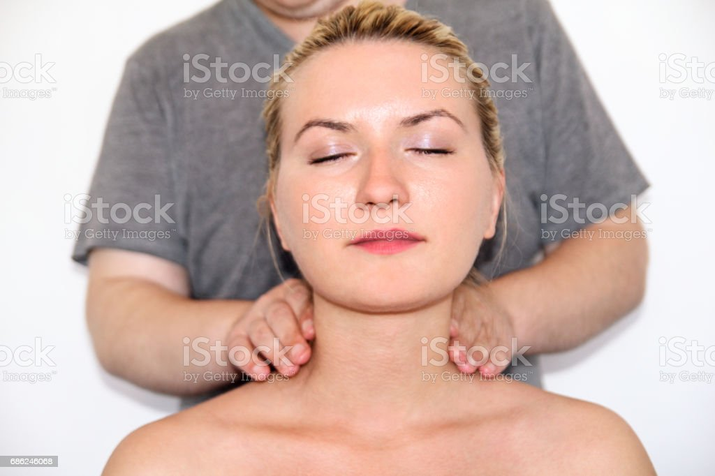 Massage relax studio. Woman having her neck massaged. Massage therapist massaging neck muscles. Body care. Beautiful young woman relaxing with hand massage at beauty body spa. stock photo