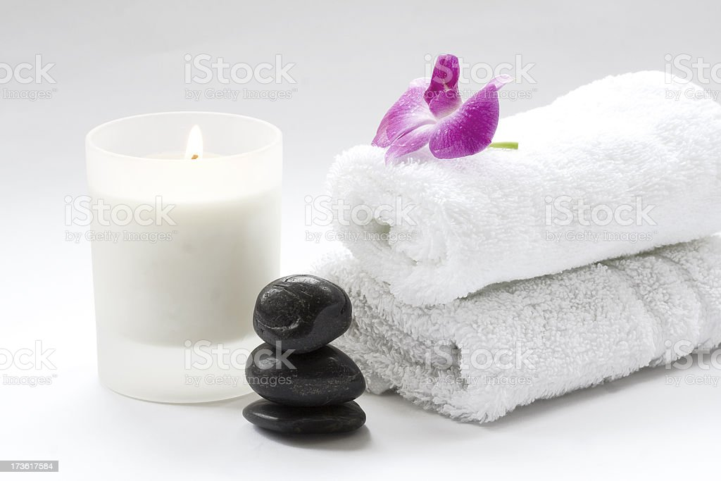 Massage stones with towels, candle and beautiful pink Orchid flower stock photo