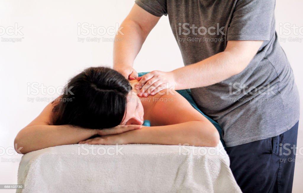 Studio de massagem. Mulher bonita descontraída com mão massagem no centro de spa de beleza. Pessoas, beleza, spa, estilo de vida saudável e conceito de relaxamento e ter mão de massagens no spa. Cuidados com o corpo. - foto de acervo