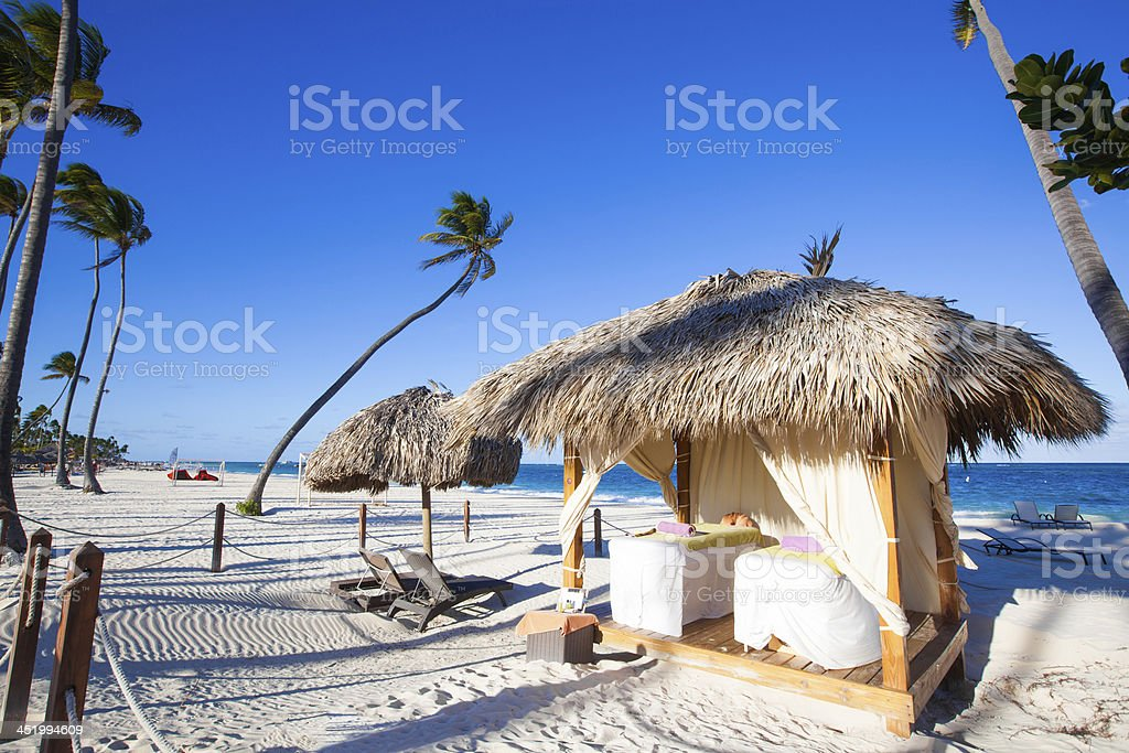 Massage tables under a hut in the beach stock photo