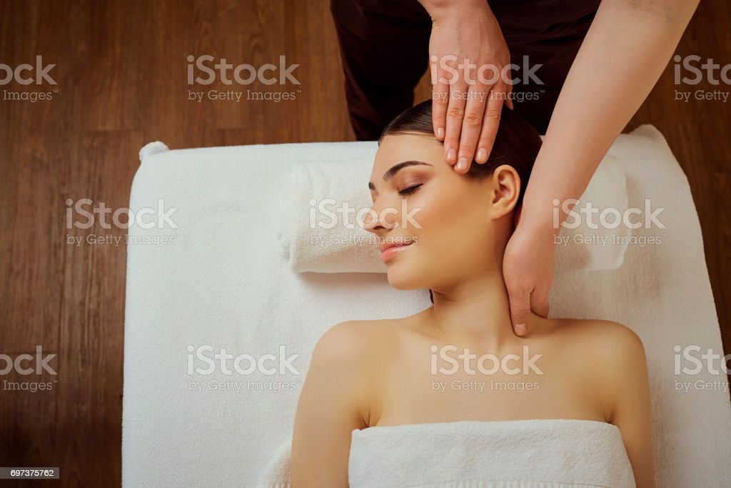 Massage the head of  neck to a young woman in massage room stock photo