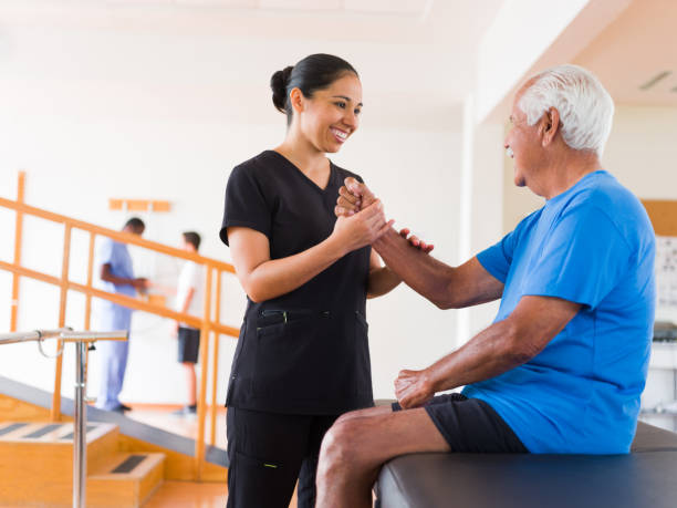 Massage therapist holding senior patient's arm and smiling stock photo