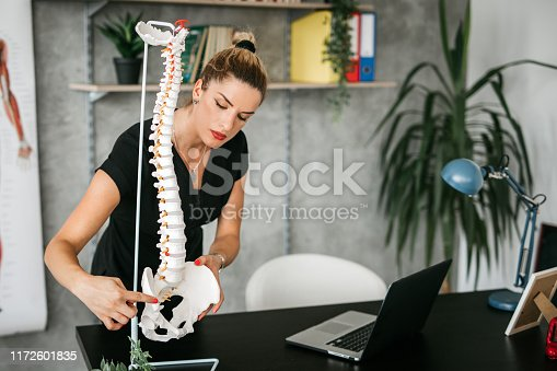 Female Massage Therapist Instructor in Anatomy Classroom preparing for class