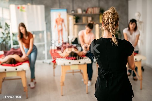 Women in massage school learning to be massage therapists