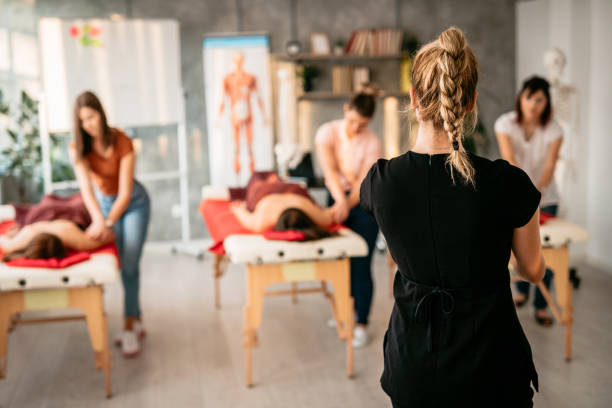 Massage therapist instructor showing practice to students stock photo