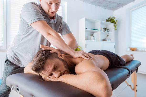 Massage therapist massaging back of the young man Physical therapist giving back massage to young man. Patient lying down on massage table. massaging stock pictures, royalty-free photos & images