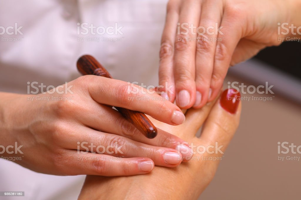 Massage therapist massaging legs of pregnant woman stock photo