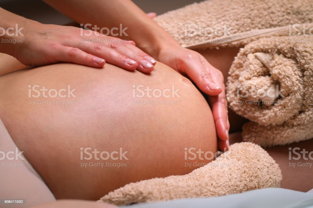 Massage therapist massaging pregnant woman stock photo