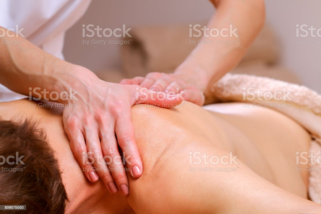 Massage therapist massaging shoulders and back of a male stock photo