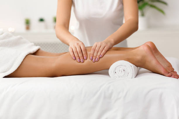 Massage therapist massaging woman calves in spa center Massage therapist massaging woman calves in spa center, side view massaging stock pictures, royalty-free photos & images