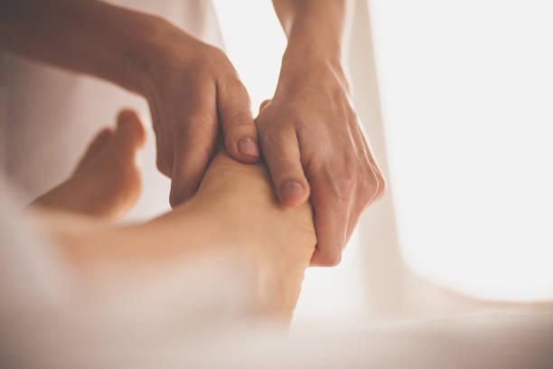 Massage therapist massaging woman's feet Close-up shot of massage therapist doing foot massage to client at spa. foot massage stock pictures, royalty-free photos & images