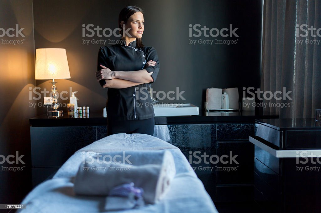 Massage therapist standing with hands crossed and looking outside stock photo