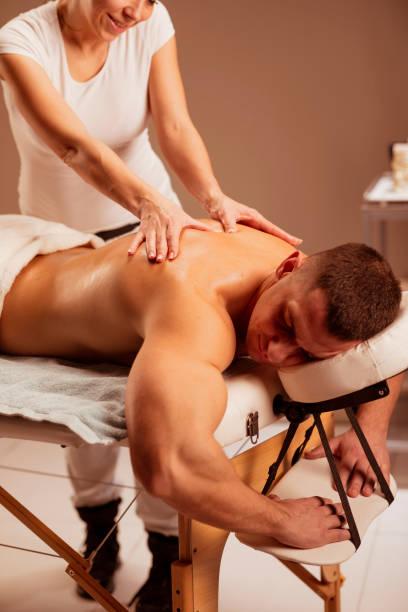Massage Therapist woman doing healing massage. Man enjoying in relaxing massaging at health spa treatment. stock photo