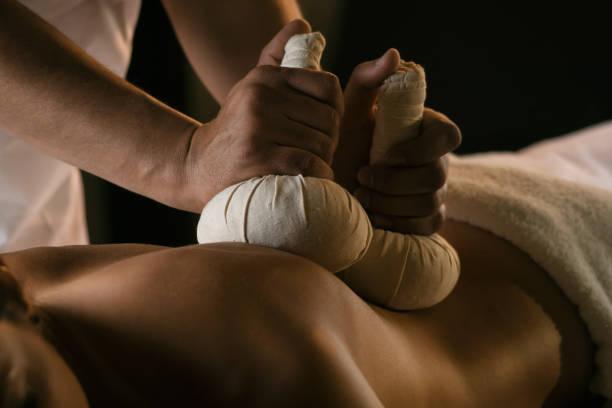 Massage with herbal balls. Luxury spa treatment stock photo