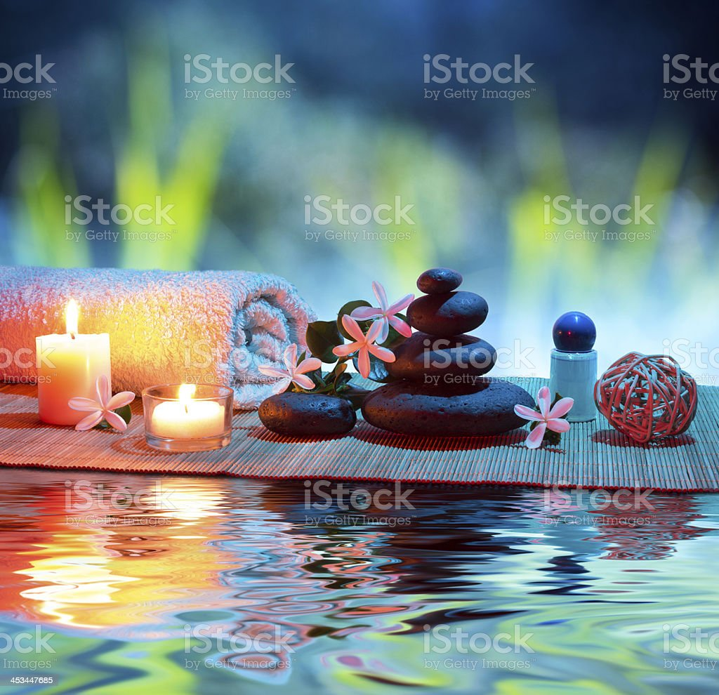 massage with tiarè and candle in garden stock photo