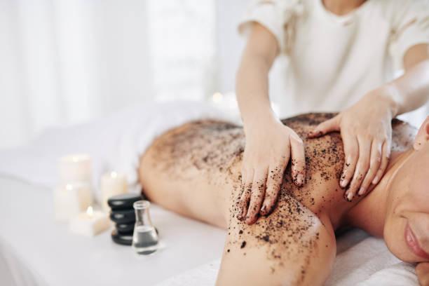 Massaging back with coffee scrub stock photo