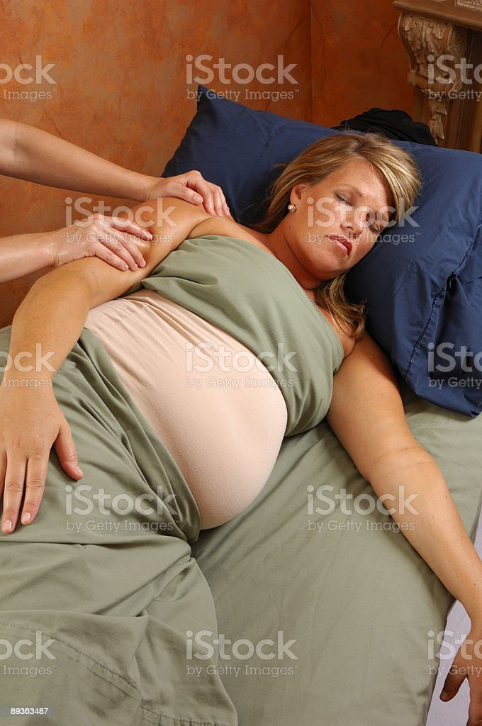 Massaging Young Pregnant Woman At Wellness Center stock photo
