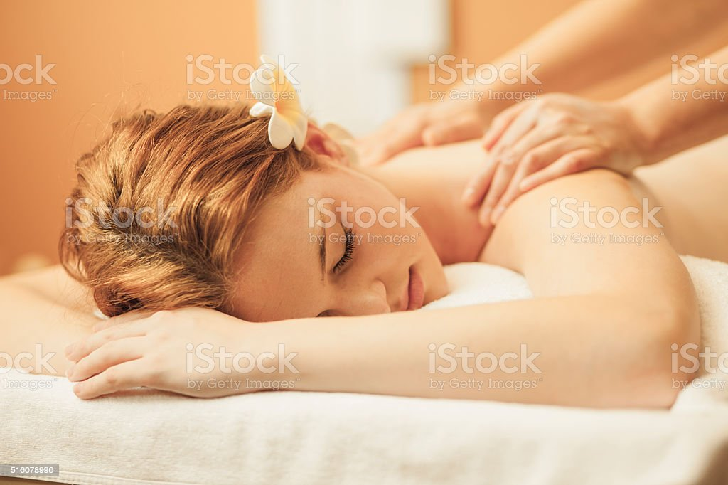 Massaging young woman's back stock photo