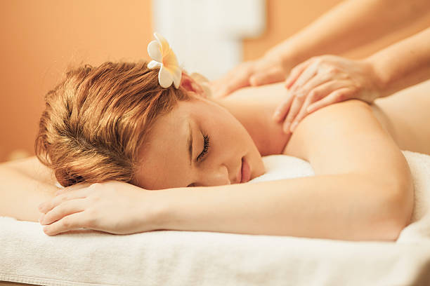 massaging young woman's back - thai massage stock photos and pictures