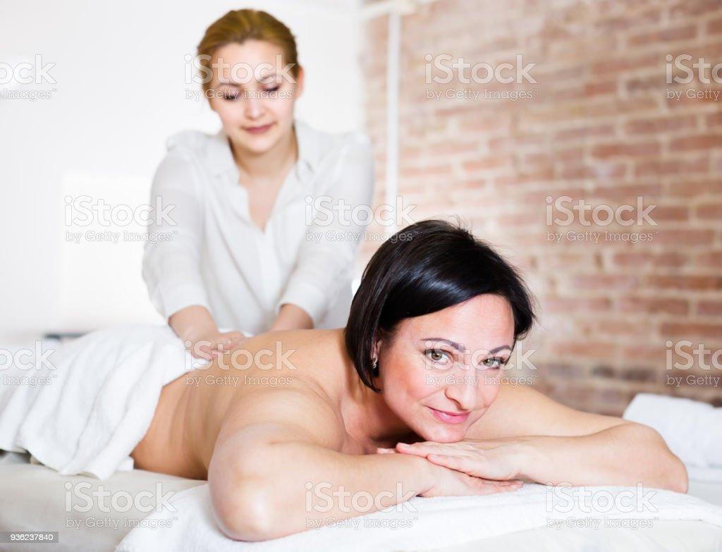 Massagist massaging back area of woman stock photo
