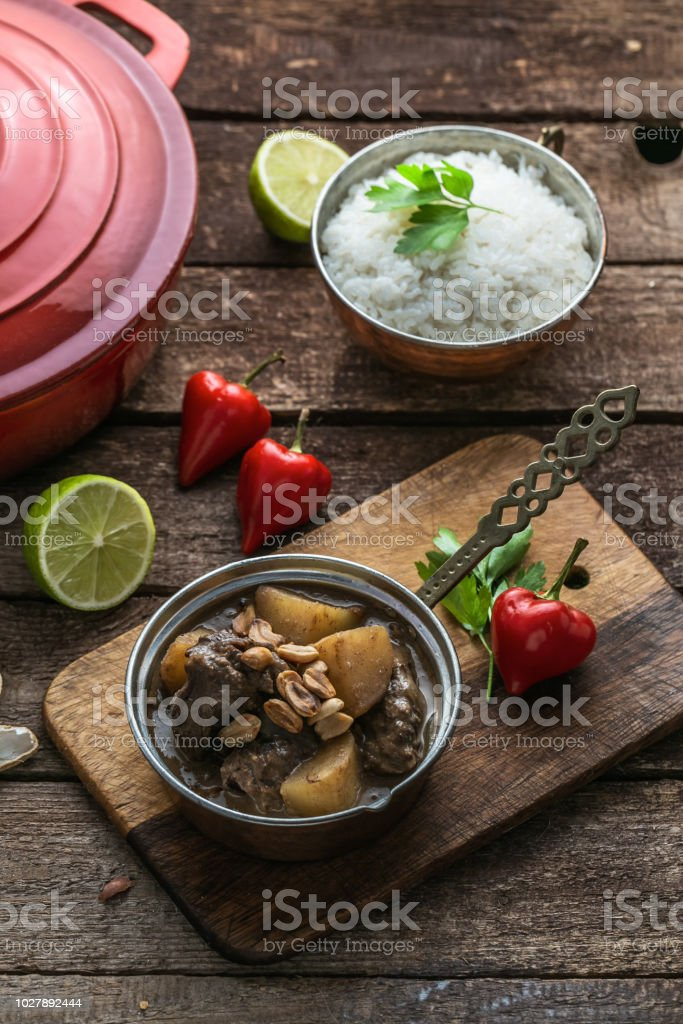 Massaman Beef Curry Served In copper pan, wooden background stock photo