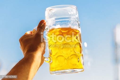 hand hunting mass-beer glasses at oktoberfest in munich against blue sky