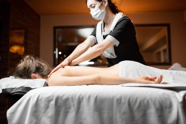 Masseur doing massage to a client stock photo