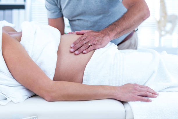 Masseur giving massage to pregnant woman stock photo