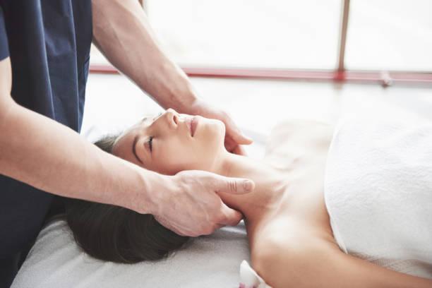 Masseur macht Entspannungsmassage für einen Hals für eine Frau. – Foto
