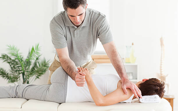 Masseur estiramiento woman's arm - foto de stock