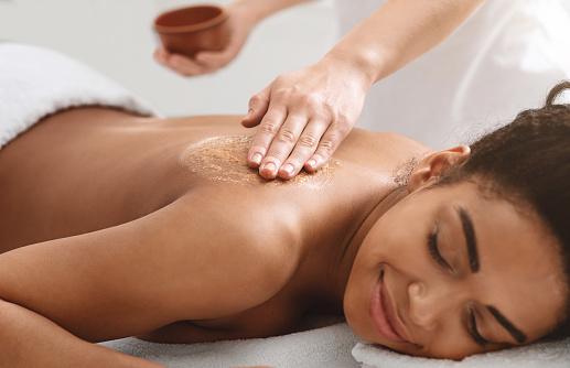 Beauty procedures at spa. Masseuse applying body scrub on black girl back, closeup