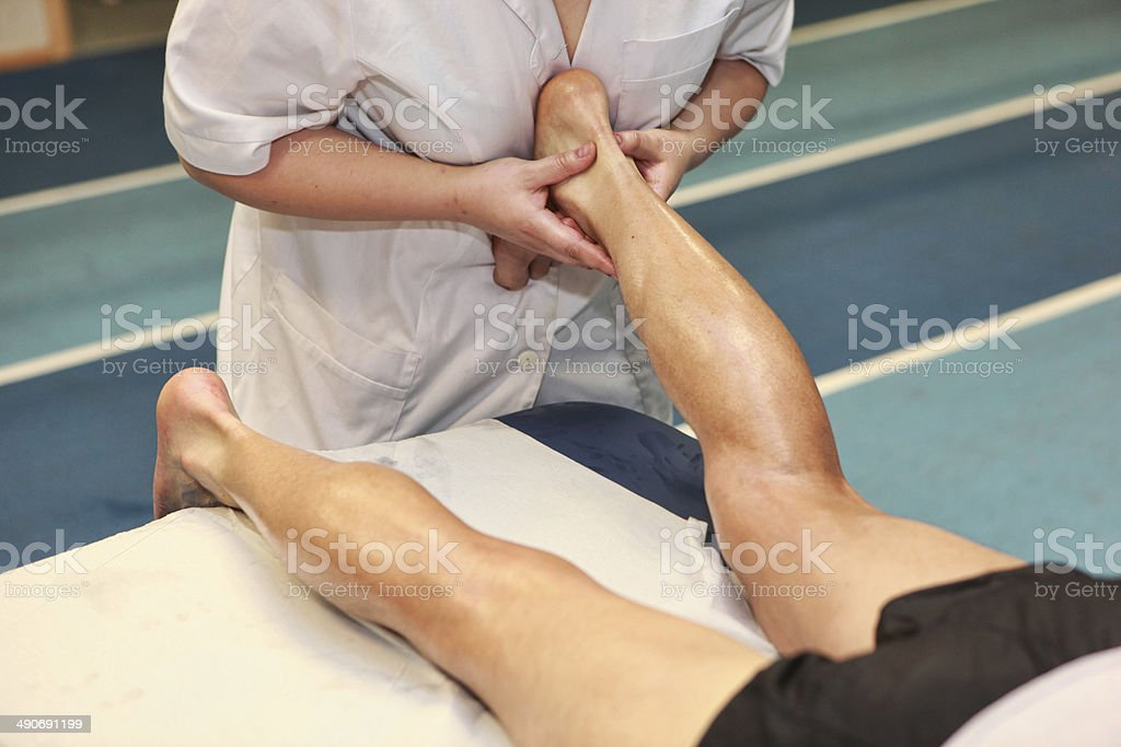 masseuse massaging athlete s Achilles tendon after running stock photo
