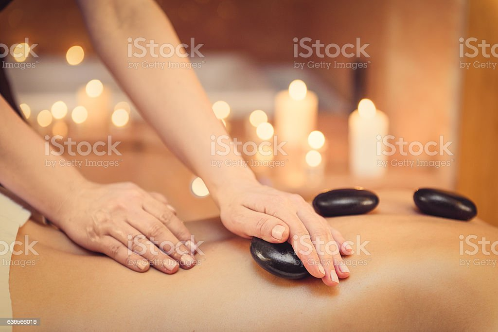 Masseuse massaging human body at spa stock photo