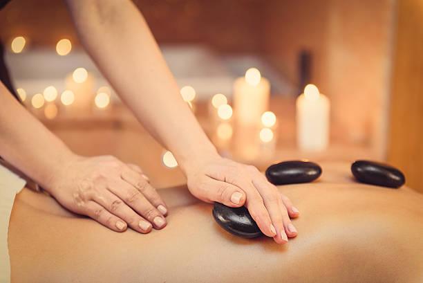Masseuse massaging human body at spa - Photo