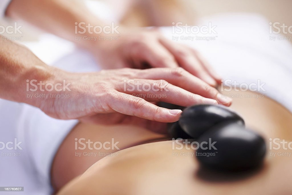 Masseuse placing hot stones on a woman's back stock photo