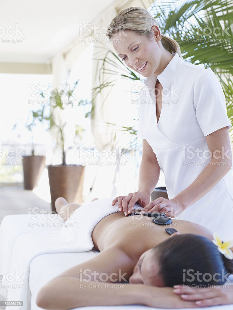 Masseuse placing massage stones on a woman's back royalty-free stock photo